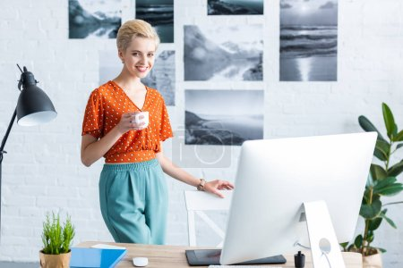 stylish female freelancer holding cup of coffee near table with graphic tablet and computer in home office