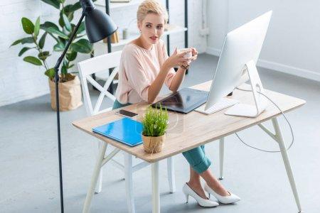 Foto de Alto ángulo de visión de mujer independiente con taza de café en mesa con tableta gráfica y equipo en oficina en casa - Imagen libre de derechos