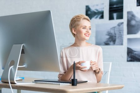 Photo for Smiling female freelancer holding cup of coffee at table with graphic tablet and computer in home office - Royalty Free Image