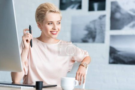 smiling female teleworker looking away at table with graphic tablet and computer in home office