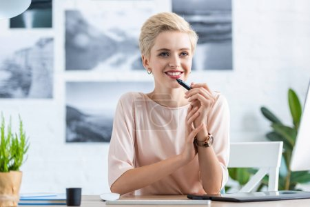 thoughtful happy female freelancer sitting at table with graphic tablet in home office