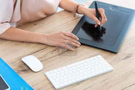 cropped image of female freelancer drawing on graphic tablet at table in home office