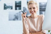 smiling female freelancer holding pen for graphic tablet in home office