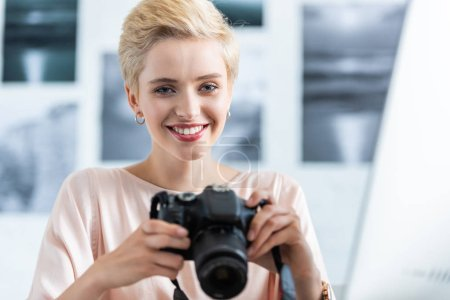 portrait of smiling female photographer holding photo camera