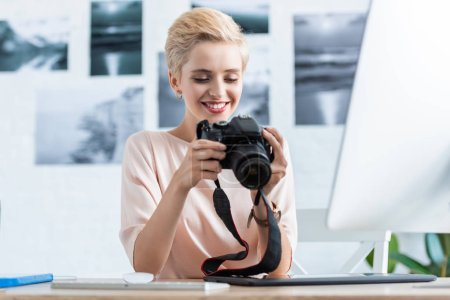 happy female photographer looking at camera screen at table with computer in home office