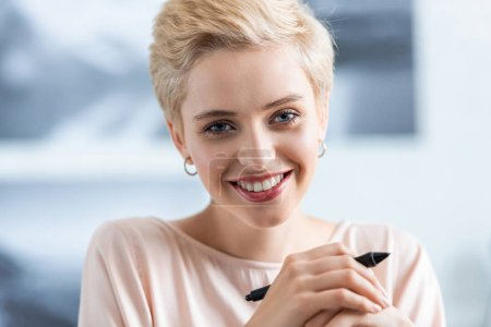 close up portrait of smiling attractive woman holding pen for graphic tablet