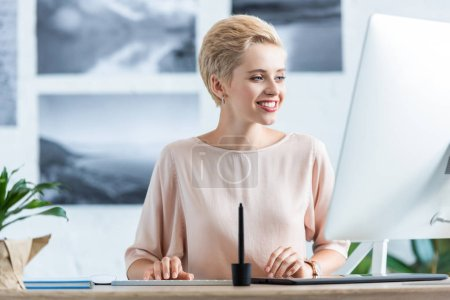 Photo for Happy businesswoman working on computer at table in office - Royalty Free Image