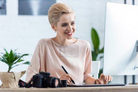 female photographer drawing on graphic tablet at table with computer and photo camera in home office