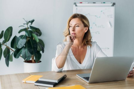 Photo pour Pensive attractive businesswoman sitting at table with laptop in office and looking away - image libre de droit