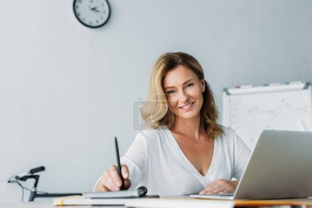 Photo for Attractive businesswoman holding pen and looking at camera in office - Royalty Free Image