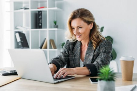 Attractive businesswoman working on laptop in office
