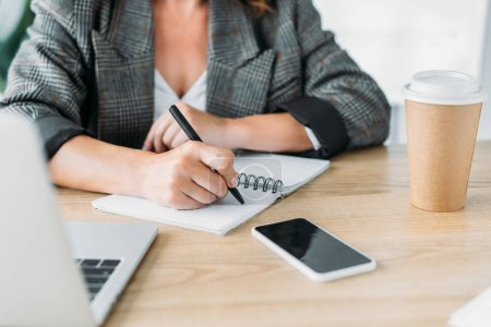 cropped image of businesswoman writing something to notebook in office