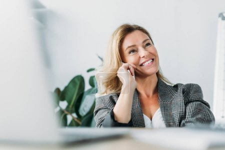 smiling attractive businesswoman talking by smartphone in office