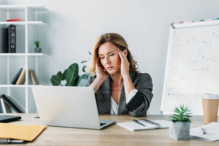 Photo for Attractive businesswoman having headache and looking at laptop in office - Royalty Free Image