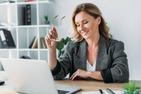 Photo pour Femme d'affaires attrayant tenant des lunettes et regardant ordinateur portable au bureau - image libre de droit