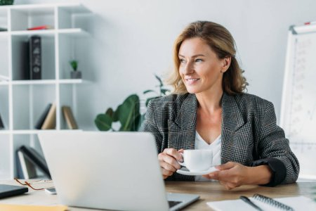 beautiful businesswoman sitting with cup of coffee at table in office and looking away