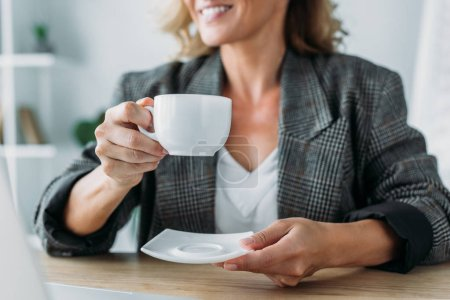 cropped image of attractive businesswoman sitting with cup of coffee at table in office