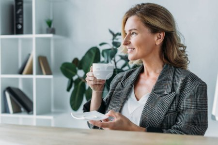 side view of attractive businesswoman drinking coffee in office