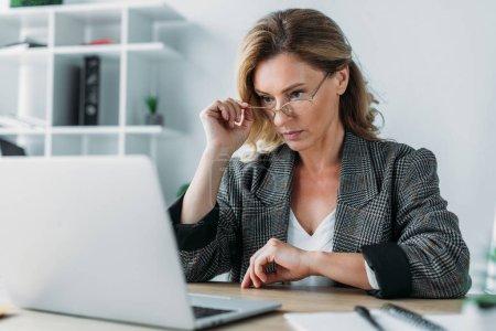 Photo pour Femme d'affaires attrayant en regardant ordinateur portable au bureau - image libre de droit