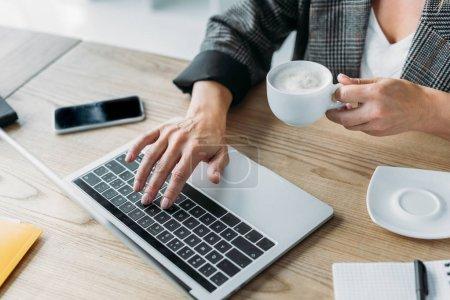 Photo pour Image recadrée de femme d'affaires à l'aide d'ordinateur portable et portefeuille tasse de café au bureau - image libre de droit