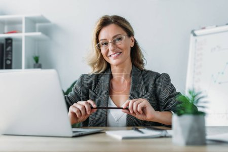 smiling attractive businesswoman sitting at table in office and looking at camera