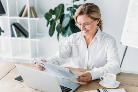 smiling attractive businesswoman reading newspaper at table with laptop in office