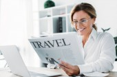 attractive businesswoman reading travel newspaper in office