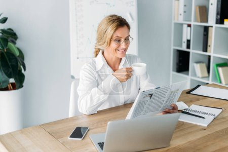 smiling attractive businesswoman drinking coffee and reading newspaper in office