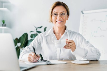 attractive businesswoman holding cup of coffee and writing to notebook in office