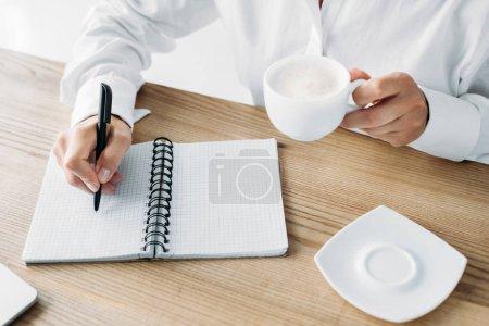 Photo pour Image recadrée femme d'affaires tenant tasse de café et l'écriture au carnet dans le bureau - image libre de droit