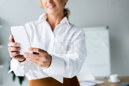 Photo for Cropped image of smiling businesswoman taking selfie with smartphone in office - Royalty Free Image