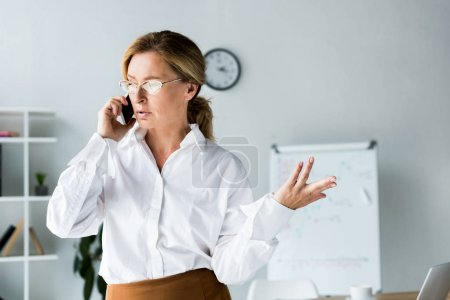 Photo for Attractive businesswoman talking by smartphone and gesturing in office - Royalty Free Image