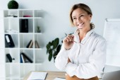smiling attractive businesswoman holding glasses and looking away in office