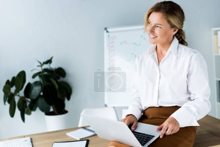 attractive businesswoman sitting on table with laptop and looking away in office