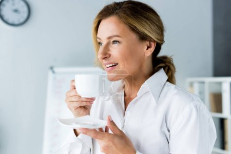 Photo pour Smiling attractive businesswoman drinking coffee in office - image libre de droit