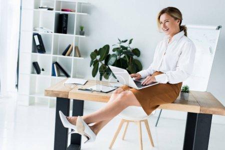 Photo pour Vue latérale de la séduisante femme d'affaires assis avec ordinateur portable sur la table au bureau - image libre de droit