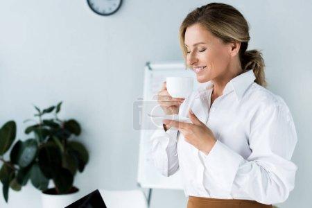 Photo pour Femme d'affaires attrayant reniflant café les yeux fermés au bureau - image libre de droit