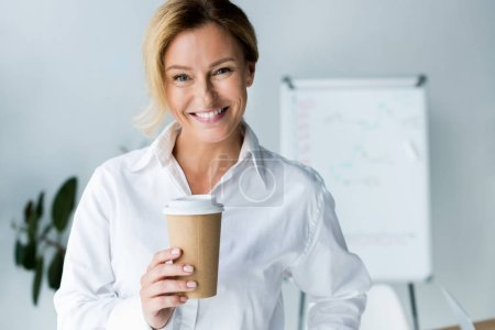 smiling attractive businesswoman holding disposable coffee cup in office and looking at camera