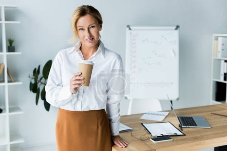 beautiful businesswoman holding disposable coffee cup in office and looking at camera
