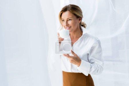 Photo pour Attrayant femme d'affaires boire du café et regarder la fenêtre dans le bureau - image libre de droit