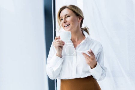 smiling beautiful businesswoman holding cup of coffee in office