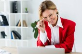 smiling attractive businesswoman touching glasses and looking at laptop in office