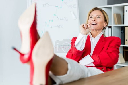 attractive businesswoman laughing and sitting with legs on table in office