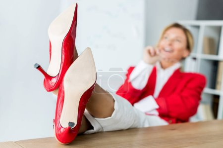 attractive businesswoman laughing and sitting with legs on table in office with red shoes on foreground