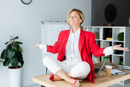 happy attractive businesswoman meditating in lotus pose on table in office