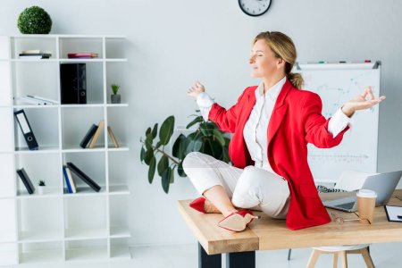 attractive businesswoman meditating in lotus pose on table in office