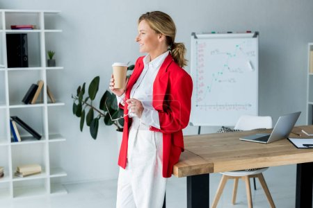 side view of attractive businesswoman standing with coffee in paper cup in office
