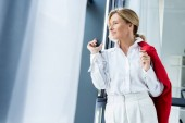 attractive businesswoman holding red jacket and looking away in office