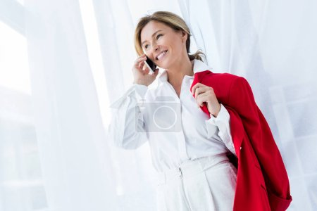 happy beautiful businesswoman holding red jacket and talking by smartphone in office