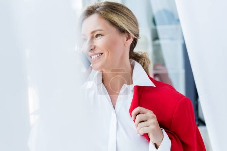 smiling attractive businesswoman holding red jacket and talking by smartphone in office